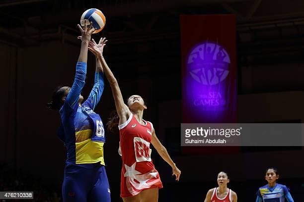Norashikin Kamalzaman of Malaysia and Lin Qingyi of Singapore challenge for the ball during the women's netball gold medal match between Singapore...