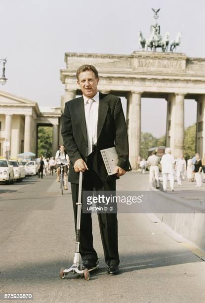 Norbert Barthle ist Mitglied des Bundestages Er fährt mit einem Tretroller durch Berlin um Staus zu entgehen Unter dem Arm hält er eine Mappe Im...