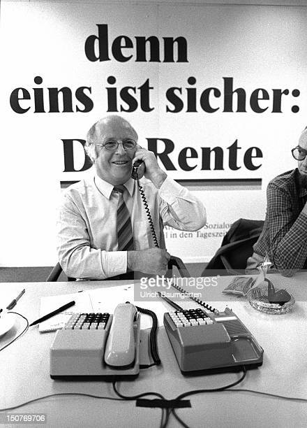 Norbert BLUEM with phone in front of the writing ' than one½s is safe The pension '