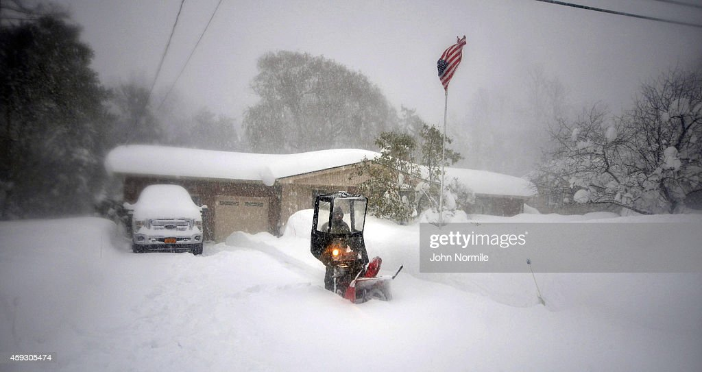 Norbert Schnorr attempts to remove some of the five feet of snow from a driveway on November 20 2014 in the suburb of Lakeview Buffalo New York The...