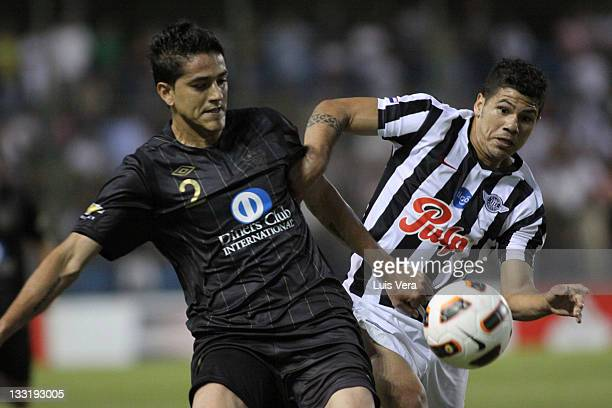 Norberto Araujo from Liga Universitaria de Quito fights for the ball with Robin Ramirez from Libertad during a match between Liga Universitaria de...