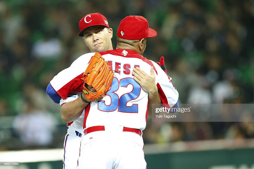 Norberto Gonzalez #33 and manager Victor Mesa of Team Cuba hug after defeating Team Japan in during Pool A, Game 6 in the first round of the 2013 World Baseball Classic at the Fukuoka Yahoo! Japan Dome on March 6, 2013 in Fukuoka, Japan.
