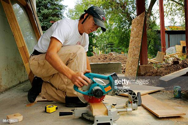 Nordic combined skier Todd Lodwick cuts a joist while renovating his basement into a rentable apartment on September 21 2005 in Steamboat Springs...