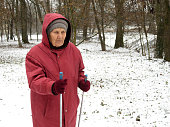 Elderly woman with sticks in winter park during snowfall, cold weather