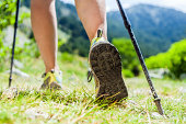 Woman hiking in mountains, adventure and exercising. Nordic walking in sunny  summer nature outdoors. Legs and sport shoes walk on grass