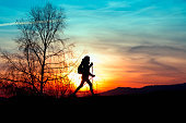 Nordic walking in the mountains at sunset colored silhouette of a girl