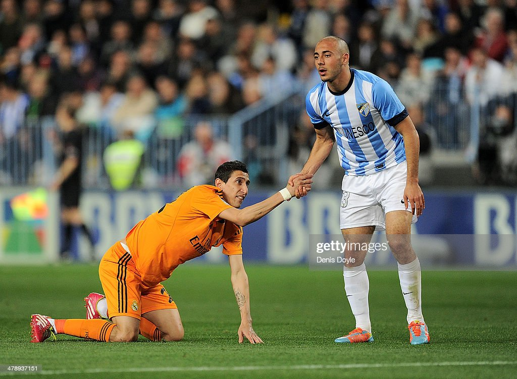 Nordin Amrabat of Malaga gives a helping hand to Angel Di Maria of Real Madrid during the La Liga match between Malaga and Real Madrid at La Rosaleda...