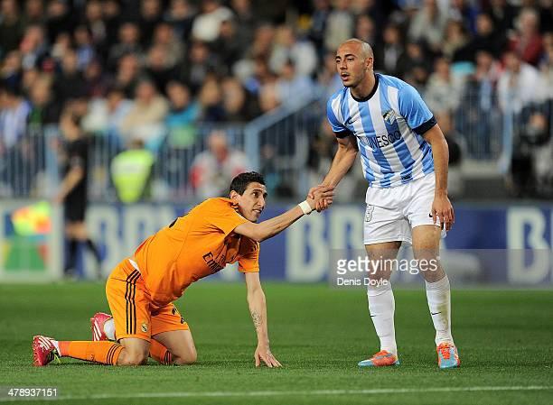 Nordin Amrabat of Malaga gives a helping hand to Angel Di Maria of Real Madrid during the La Liga match between Malaga and Real Madrid at La Rosaleda...