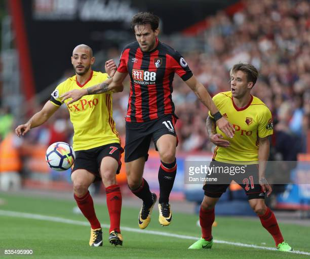 Nordin Amrabat of Watford and Kiko Femenia of Watford attempt to tackle Charlie Daniels of AFC Bournemouth during the Premier League match between...