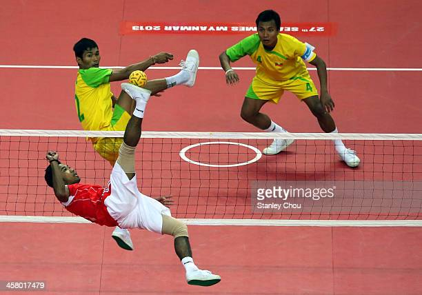 Norfrisal of Indonesia battles with Alung Pyah Tun of Burma while Kyaw Soe Win looks on during the Men's Team Double Final of the Sepak Takraw...