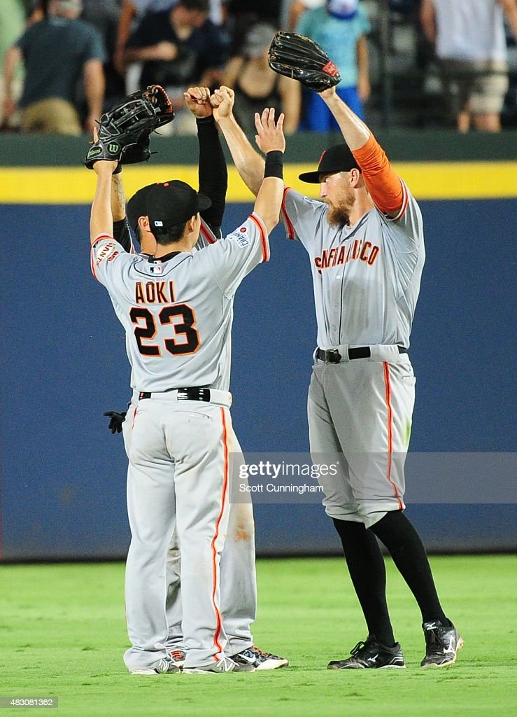 Nori Aoki #23, Hunter Pence #8, and Gregor Blanco #7 (obscured) of the San Francisco Giants celebrate after the game against the Atlanta Braves at Turner Field on August 5, 2015 in Atlanta, Georgia.