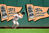 Nori Aoki of the San Francisco Giants goes up against the wall to catch a fly ball off the bat of Jason Castro of the Houston Astros in the top of...