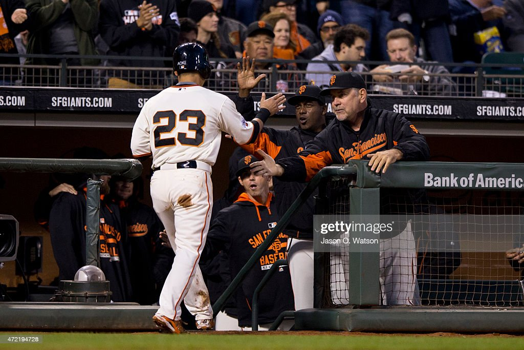 Nori Aoki #23 of the San Francisco Giants is congratulated by manager Bruce Bochy #15 after scoring a run against the San Diego Padres during the third inning at AT&T Park on May 4, 2015 in San Francisco, California.