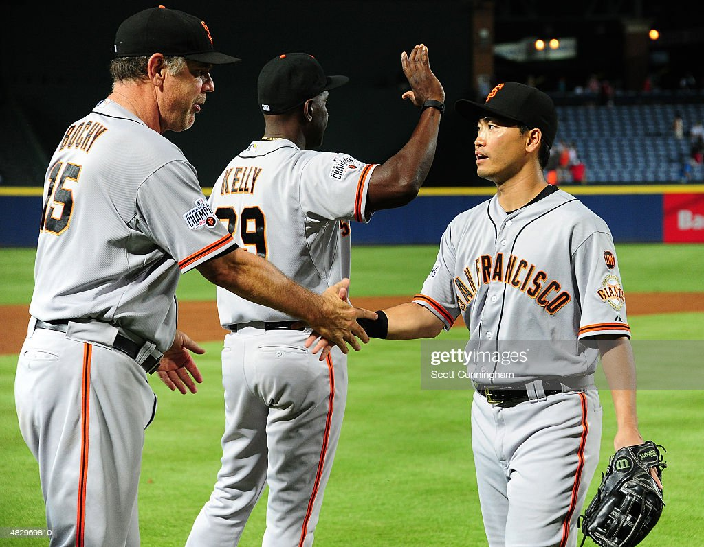 Nori Aoki #23 (R) of the San Francisco Giants is congratulated by Manager Bruce Bochy #15 after the game against the Atlanta Braves at Turner Field on August 4, 2015 in Atlanta, Georgia.
