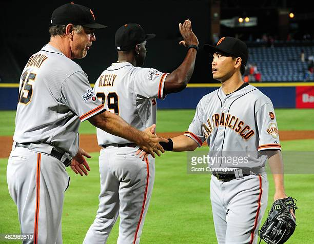 Nori Aoki of the San Francisco Giants is congratulated by Manager Bruce Bochy after the game against the Atlanta Braves at Turner Field on August 4...