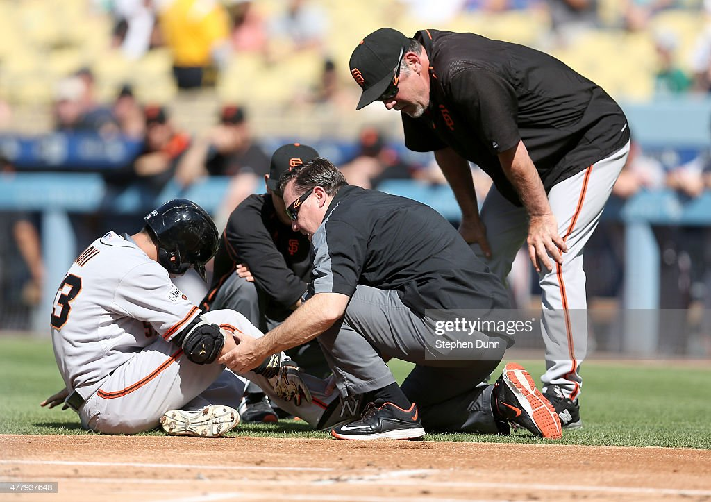 Nori Aoki #23 of the San Francisco Giants is tended to by Giants' trainers as manager Bruce Bochy (R) looks on after Aoki was hit in the ankle by a pitch in the first inning against the Los Angeles Dodgers at Dodger Stadium on June 20, 2015 in Los Angeles, California.