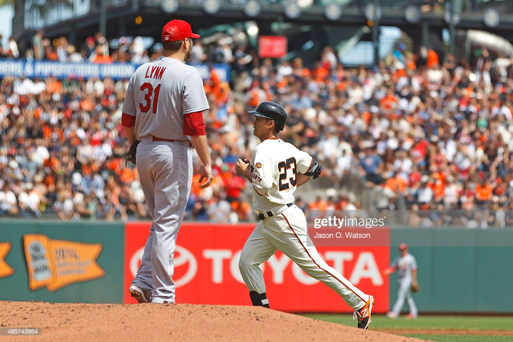 Nori Aoki of the San Francisco Giants runs to the dugout past Lance Lynn of the St Louis Cardinals after hitting a fly ball for an out during the...