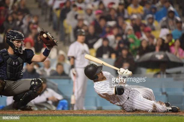 Norichika Aoki of team Japan dives away from an inside pitch in the eighth inning against team United States during Game 2 of the Championship Round...