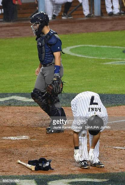 Norichika Aoki of team Japan takes off his gear as he walks to first base in the eighth inning against team United States during Game 2 of the...
