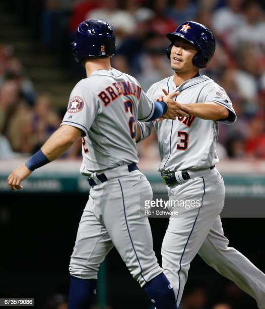 Norichika Aoki of the Houston Astros celebrates with Alex Bregman after scoring on a double by Marwin Gonzalez off Bryan Shaw of the Cleveland...