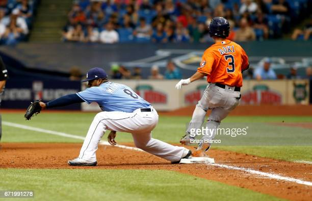 Norichika Aoki of the Houston Astros reaches first base ahead of first baseman Rickie Weeks of the Tampa Bay Rays on an infield single during the...