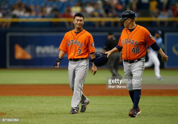 Norichika Aoki of the Houston Astros speaks with first base coach Rich Dauer as they walk in following the top of the second inning of a game against...