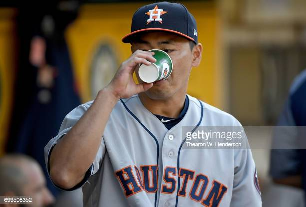 Norichika Aoki of the Houston Astros takes a drink of water in the dugout prior to the start of their game against the Oakland Athletics at Oakland...