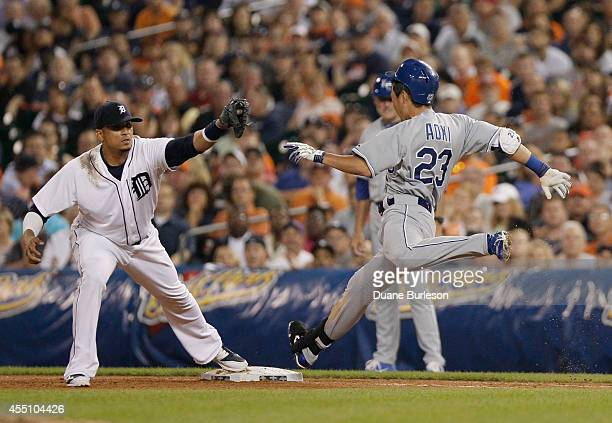 Norichika Aoki of the Kansas City Royals can't beat the throw to first baseman Victor Martinez of the Detroit Tigers during the seventh inning of a...