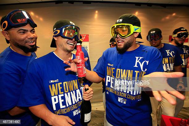 Norichika Aoki of the Kansas City Royals celebrates with teammates Kelvin Herrera and Francisley Bueno in the locker room after their 2 to 1 win over...