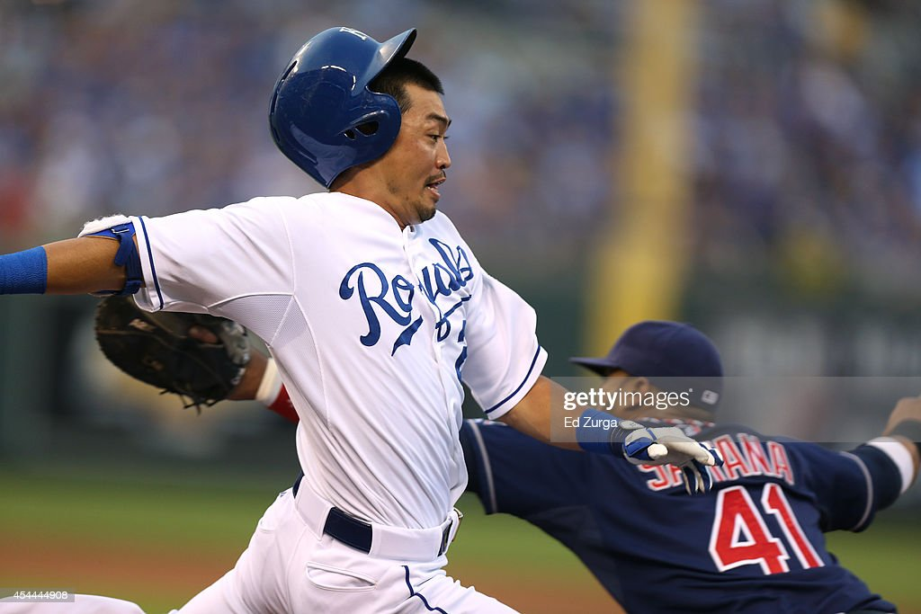Norichika Aoki #23 of the Kansas City Royals crosses first base as he out runs the throw to Carlos Santana #41 of the Cleveland Indians for a single in the first at Kauffman Stadium on August 31, 2014 in Kansas City, Missouri.
