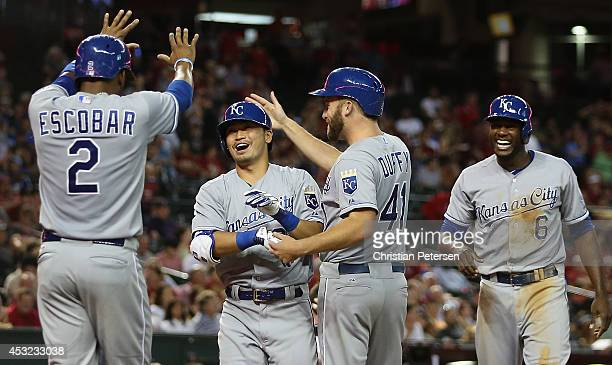 Norichika Aoki of the Kansas City Royals is congratulated by Alcides Escobar Danny Duffy and Lorenzo Cain after Aoki hit a grand slam against the...