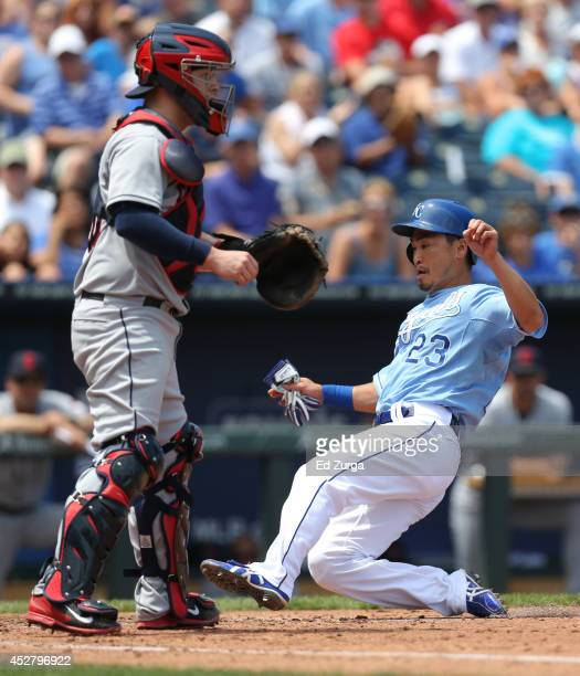 Norichika Aoki of the Kansas City Royals slides into home past Roberto Perez of the Cleveland Indians as he scores on a Alex Gordon sacrifice fly in...