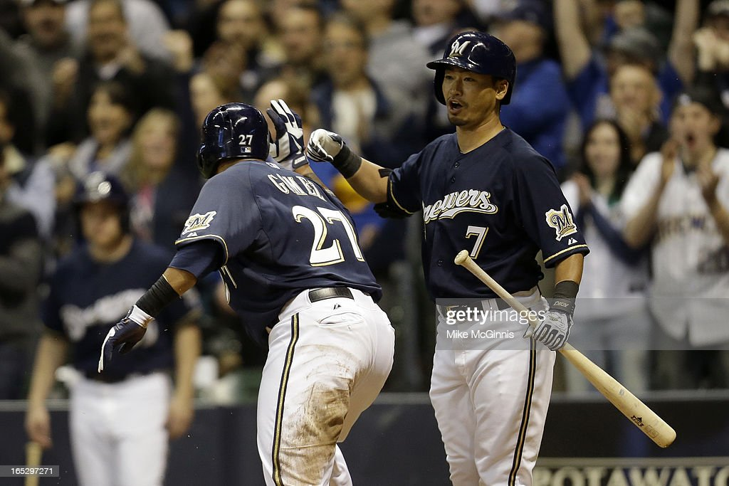 <a gi-track='captionPersonalityLinkClicked' href=/galleries/search?phrase=Norichika+Aoki&family=editorial&specificpeople=850957 ng-click='$event.stopPropagation()'>Norichika Aoki</a> #7 of the Milwaukee Brewers celebrates with Carlos Gomez #27 after he crosses home plate during the bottom of the second inning against the Colorado Rockies at Miller Park on April 2, 2013 in Milwaukee, Wisconsin.