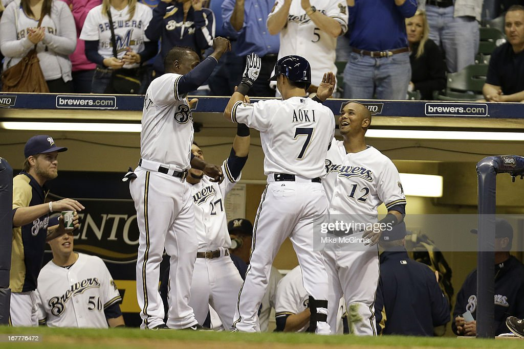 Norichika Aoki #7 of the Milwaukee Brewers celebrates with Yuniesky Betancourt #3 and Martin Maldonado outside the dugout after hitting a solo home run in the bottom of the fourth inning against the Pittsburgh Pirates during the game at Miller Park on April 29, 2013 in Milwaukee, Wisconsin.