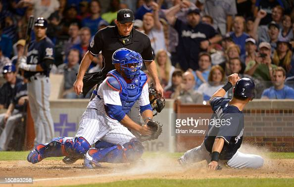Norichika Aoki of the Milwaukee Brewers scores past catcher Welington Castillo of the Chicago Cubs after teammate Rickie Weeks became involved in a...