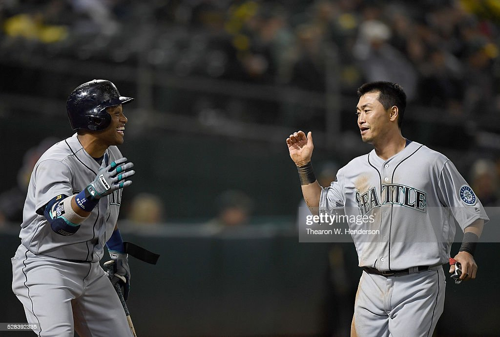 Norichika Aoki #8 of the Seattle Mariners is congratulated by Robinson Cano #22 after Aoki scored against the Oakland Athletics in the top of the seventh inning at O.co Coliseum on May 2, 2016 in Oakland, California.