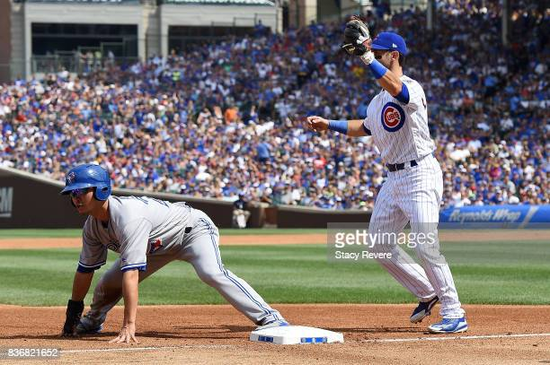 Norichika Aoki of the Toronto Blue Jays beats a tag at third base by Tommy La Stella of the Chicago Cubs during the fifth inning of a game at Wrigley...