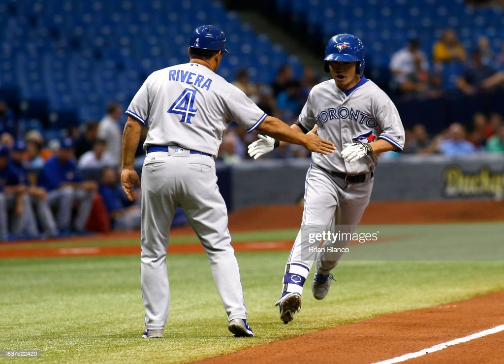 Norichika Aoki #23 of the Toronto Blue Jays celebrates with third base coach Luis Rivera #4 after hitting a home run off of pitcher Chris Archer of the Tampa Bay Rays during the first inning of a game on August 22, 2017 at Tropicana Field in St. Petersburg, Florida.