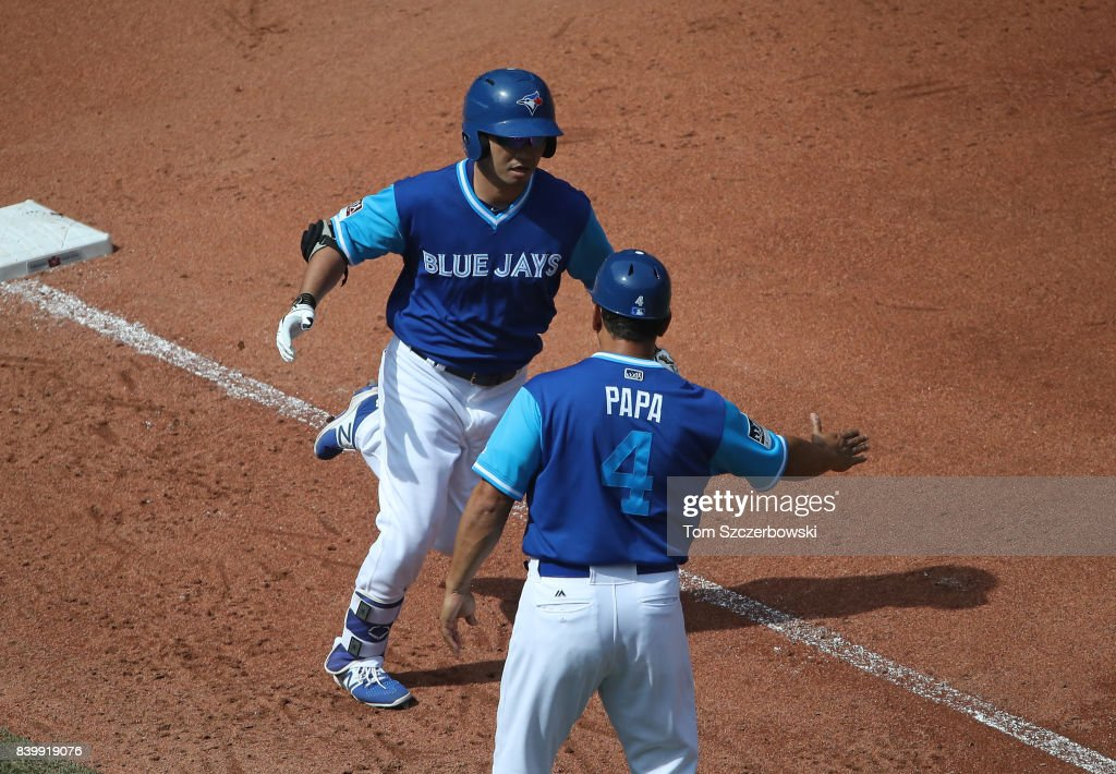 Norichika Aoki #23 of the Toronto Blue Jays is congratulated by third base coach Luis Rivera #4 after hitting a solo home run in the fourth inning during MLB game action against the Minnesota Twins at Rogers Centre on August 27, 2017 in Toronto, Canada.