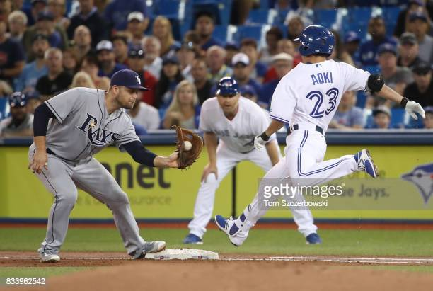 Norichika Aoki of the Toronto Blue Jays is thrown out at first base on a soft grounder in the first inning during MLB game action as Lucas Duda of...