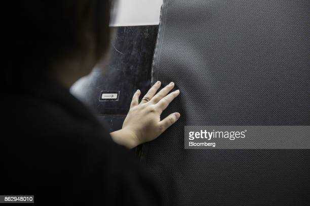 Noriko Oda inspection manager at Hironen Textile Industry Co checks a sheet of material at a company factory in Sakai Fukui Prefecture Japan on...