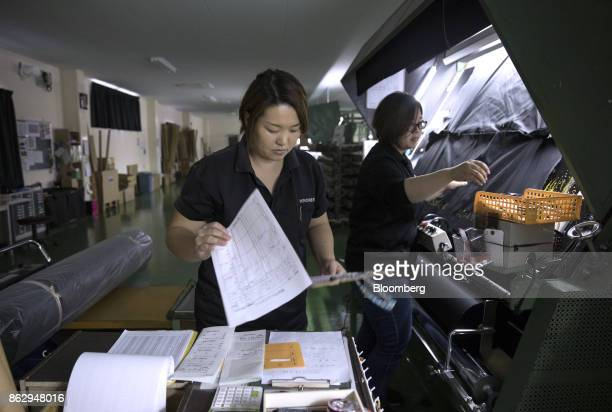 Noriko Oda inspection manager at Hironen Textile Industry Co checks papers at a company factory in Sakai Fukui Prefecture Japan on Tuesday Oct 10...