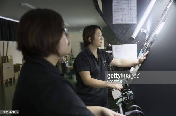 Noriko Oda inspection manager at Hironen Textile Industry Co right checks a sheet of material at a company factory in Sakai Fukui Prefecture Japan on...