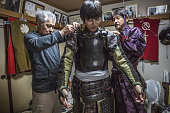 Norio Isami center is dressed by his father Masayuki Isami right and Koichi Kamata in traditional samurai clothing while getting ready at home for...
