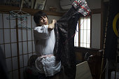 Norio Isami dresses himself in traditional samurai clothing while getting ready at home for the Soma Nomaoi festival in Minamisoma Fukushima...