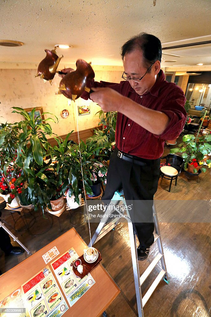 Noriyuki Tsuzuki, on a stepladder, pours coffee and milk into a mug from a height of 2.5 metres at Tsuzuki & Lintong Coffee House on November 27, 2013 in Nagoya, Aichi, Japan. When ordered a 500 yen (4.9 U.S. dollars) cafe au lait, owner Noriyuki Tsuzuki pulls up a stepladder alongside the customer's table and climbs it. Then, holding a pot of coffee in his right hand and a pot of milk in his left, the 64-year-old pours both simultaneously from a height of 2.5 metres into a mug on the table to have a bigger impact and please customers.