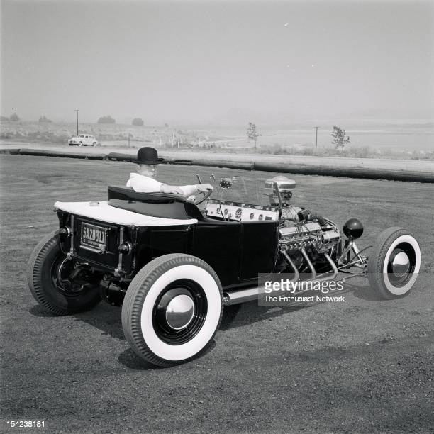Norm Grabowski in his derby hat sits with his arm up on the seat of his wild custom roadster with supercharged Cadillac engine chopped '32 Ford shell...