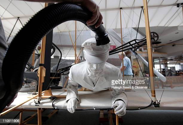 Norm Kellett cleans off seventeen years of dust from Orville Wright of the fullscale reproduction 1903 Wright Flyer Monday March 21 2011 Norm and his...