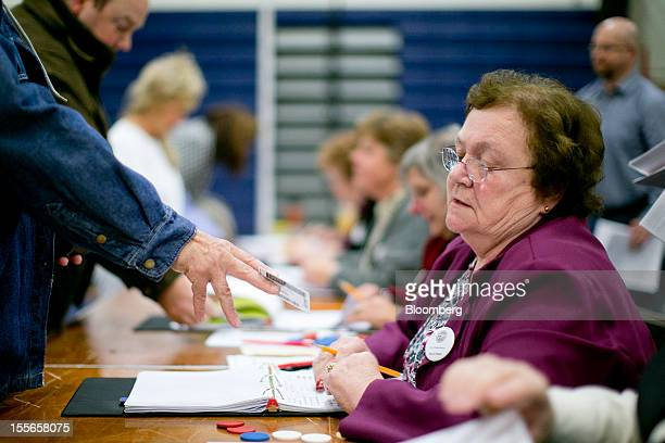 Norma Boyce checks voter identification at a polling station in Manchester New Hampshire US on Tuesday Nov 6 2012 US President Obama is seeking to...