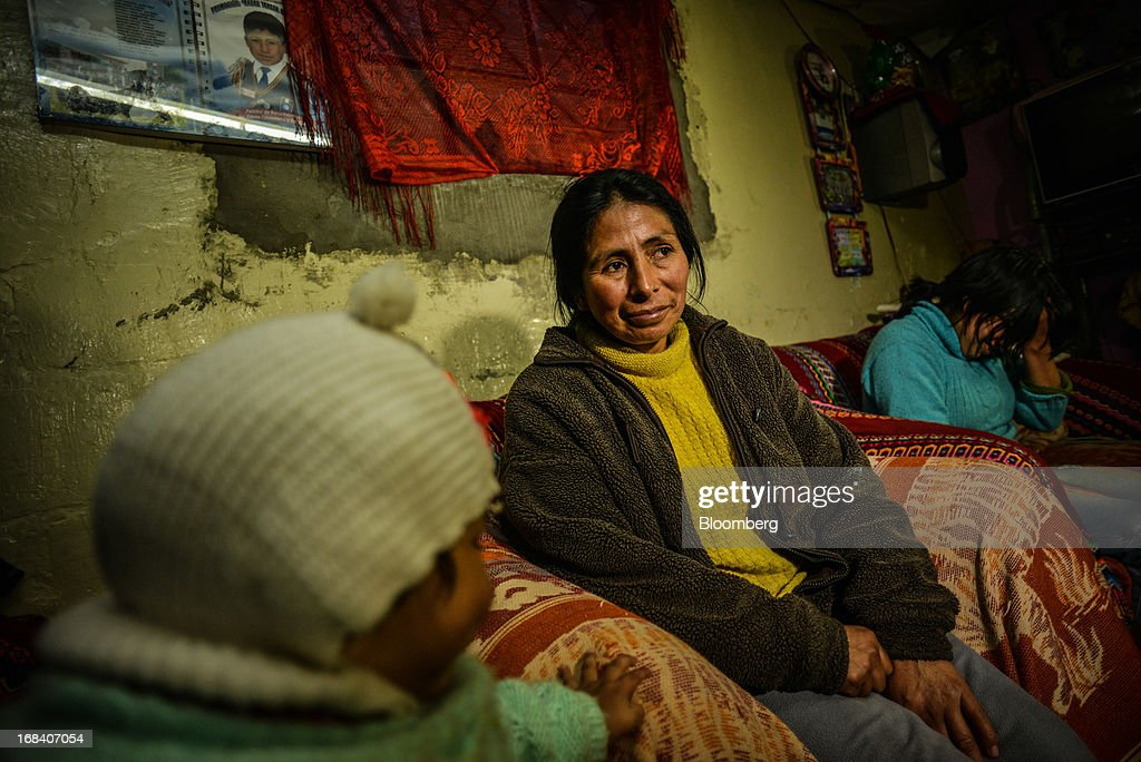 Norma Figueroa sits with her family on a couch in the town of La Oroya, Peru, on Tuesday, March 19, 2013. In La Oroya, some parents say they believe Doe Run Peru plantís toxins stunted their children's bodies and damaged their minds. Photographer: Meridith Kohut/Bloomberg via Getty Images
